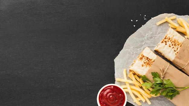 Vista superior de um delicioso kebab com ketchup e batatas fritas Foto gratuita