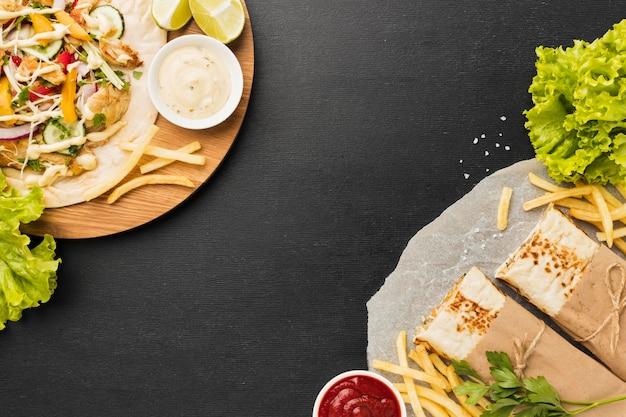 Vista superior de um delicioso kebab com salada e batatas fritas Foto gratuita