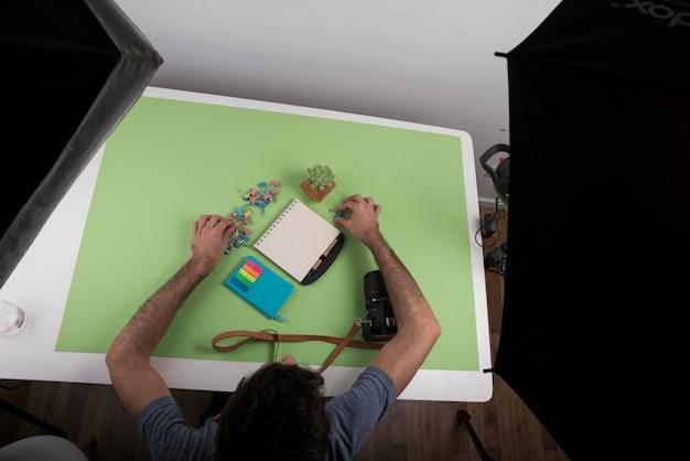 Vista superior, de, um, pessoa, organizando, papelaria, sobre, tabela, perto, câmera, e, planta suculenta, em, estúdio Foto gratuita