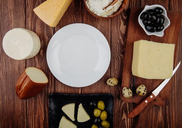 Vista superior de um prato branco vazio e diferentes tipos de queijo com azeitonas em conserva e ovos de codorna, dispostas na mesa rústica Foto gratuita