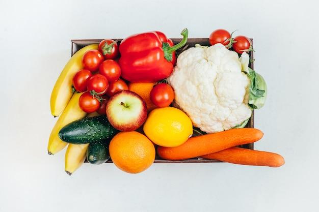 Vista superior de uma caixa com vegetais e frutas em uma superfície branca Foto Premium