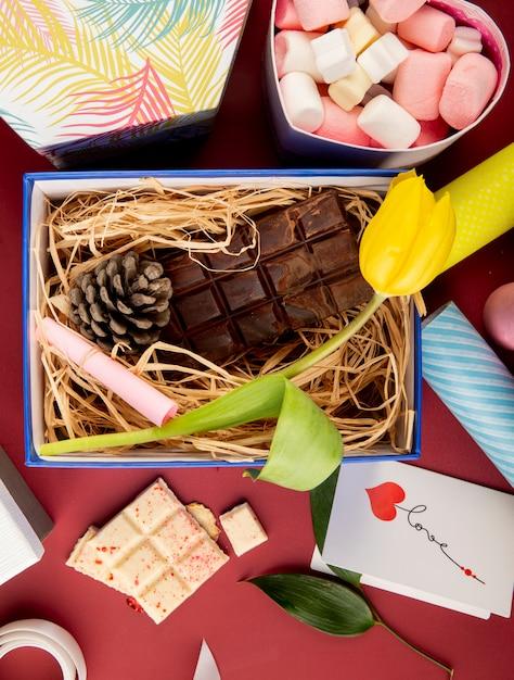 Vista superior de uma caixa de presente aberta com flor de tulipa de cor amarela, barra de chocolate escura, cone e palha e uma caixa em forma de coração cheia de marshmallow na mesa vermelha escura Foto gratuita