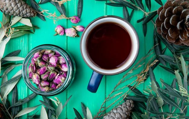 Vista superior de uma caneca de chá com botões de rosa de chá seco em uma jarra de vidro em madeira verde Foto gratuita