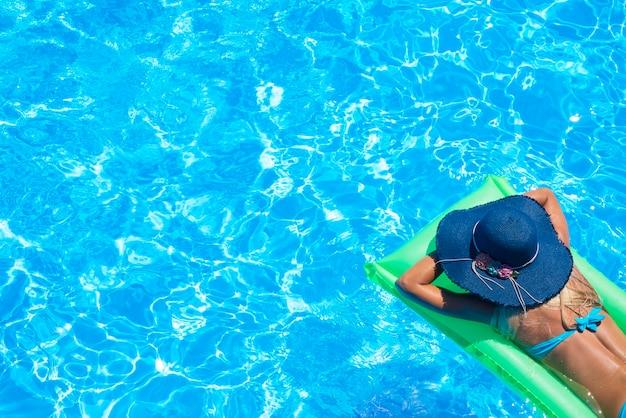 Vista superior de uma jovem magra de biquíni no colchão de ar verde na piscina Foto gratuita