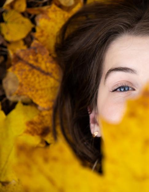 Vista superior de uma menina bonito com olhos azuis, que na queda se encontra na terra e prende uma folha de plátano amarela bonita na frente dela. Foto Premium