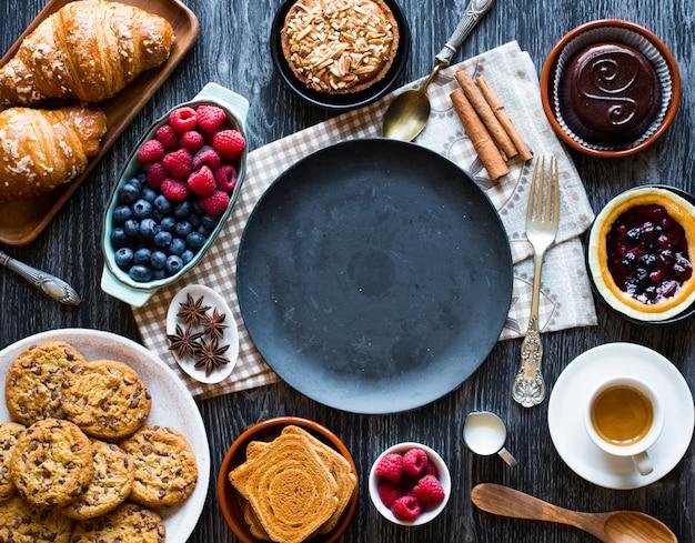 Vista superior de uma mesa de madeira cheia de bolos, frutas, café, biscoitos, especiarias e muito mais Foto Premium