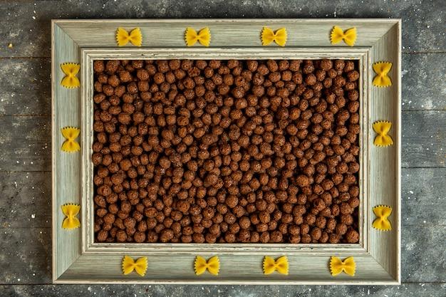 Vista superior de uma moldura de madeira com macarrão farfalle e preenchido com bolas de milho de cereais de chocolate Foto gratuita