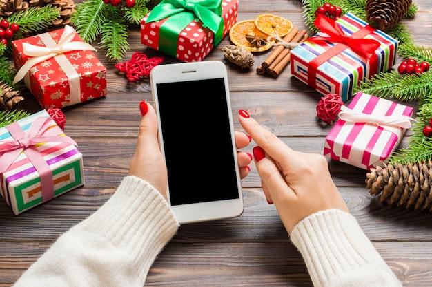 Vista superior de uma mulher segurando um telefone na mão no ano novo de madeira feito de abeto e decorações festivas. Foto Premium