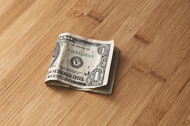 Vista superior de uma nota de um dólar americano em uma superfície de madeira Foto gratuita