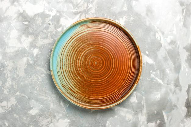 Vista superior de uma panela marrom redonda vazia isolada em uma superfície cinza clara Foto gratuita