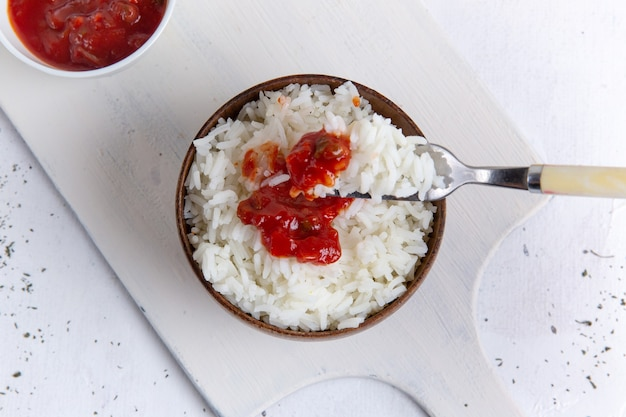 Vista superior de uma saborosa refeição de arroz cozido dentro de uma panela marrom com molho picante vermelho na superfície branca Foto gratuita