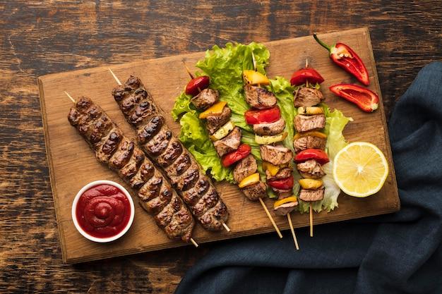 Vista superior de uma tábua de cortar com delicioso kebab e limão Foto gratuita