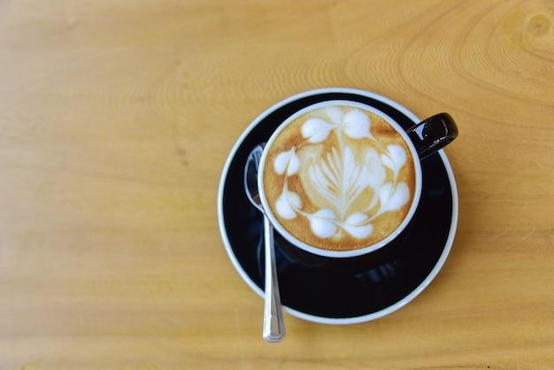 Vista superior de uma xícara de café, arte capuccino, latte art, café com leite quente, cappuccino na mesa de madeira no café Foto Premium