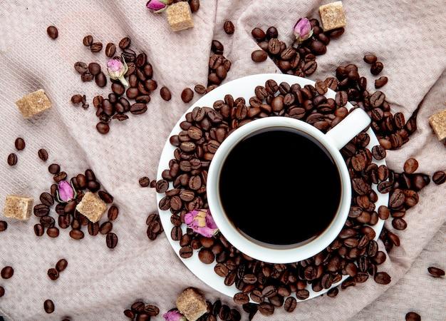 Vista superior de uma xícara de café com grãos de café, cubos de açúcar mascavo e botões de rosa chá Foto gratuita