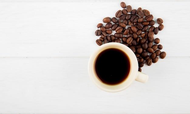Vista superior de uma xícara de café e grãos de café espalhados em fundo branco, com espaço de cópia Foto gratuita
