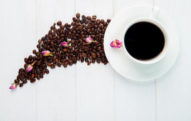 Vista superior de uma xícara de café e grãos de café espalhados no fundo branco Foto gratuita