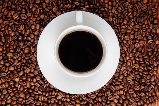 Vista superior de uma xícara de café sobre fundo de grãos de café Foto gratuita