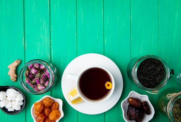 Vista superior de uma xícara de chá com frutas secas e botões de rosa secos com folhas de chá preto em frascos de vidro em madeira verde com espaço de cópia Foto gratuita