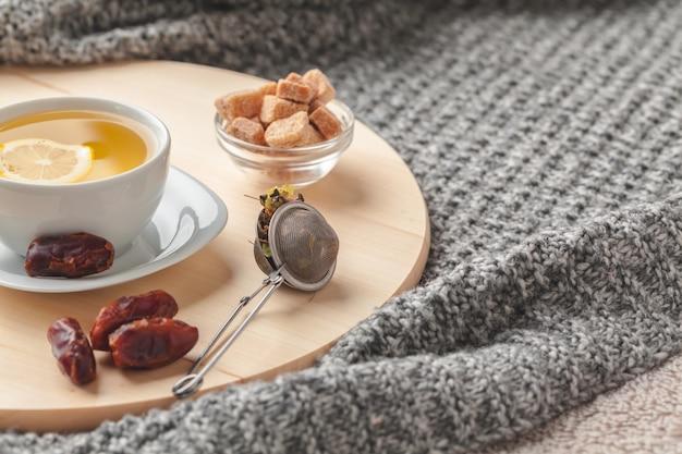 Vista superior de uma xícara de chá com um pedaço de limão na mesa de madeira Foto Premium