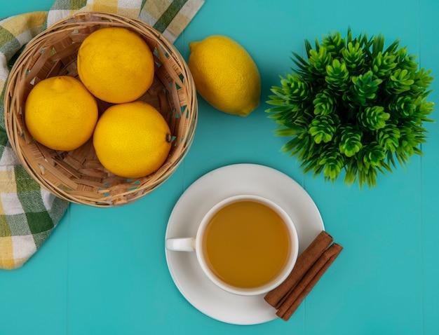 Vista superior de uma xícara de chá e canela no pires com uma cesta de limões em um pano xadrez sobre fundo azul Foto gratuita