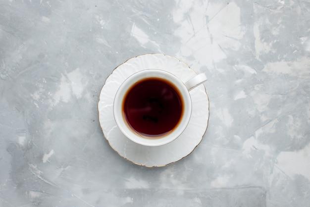 Vista superior de uma xícara de chá quente dentro de uma xícara branca acesa, bebida de chá doce Foto gratuita