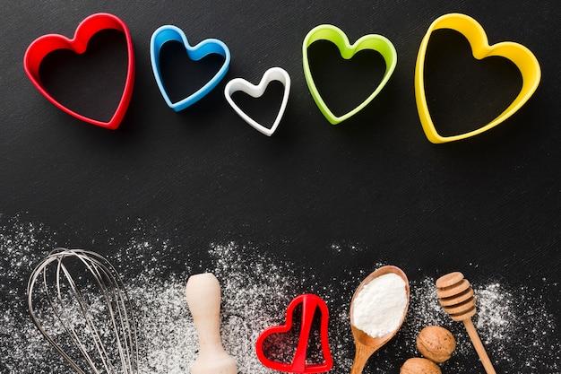 Vista superior de utensílios de cozinha com formas de coração coloridas e farinha Foto gratuita