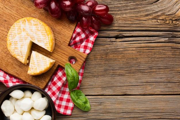Vista superior de uvas e queijo com espaço de cópia Foto gratuita