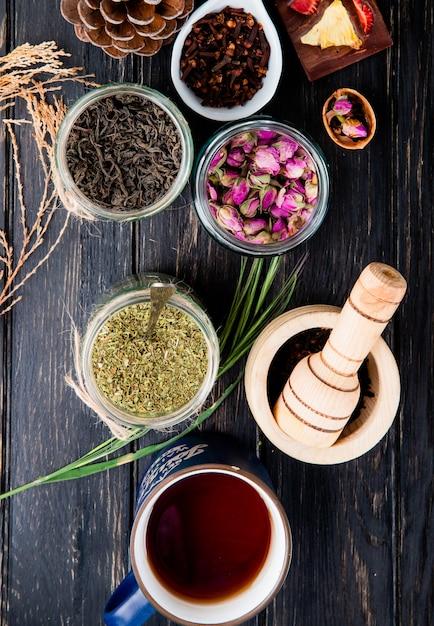 Vista superior de várias especiarias e ervas secas folhas de chá preto, hortelã, botões de rosa, tempero de cravo e pimenta preta em potes de vidro em madeira preta Foto gratuita