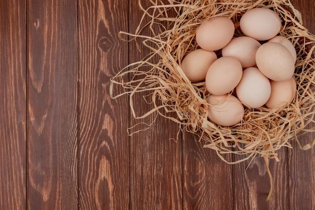Vista superior de vários ovos de galinha fresca no ninho em um fundo de madeira com espaço de cópia Foto gratuita