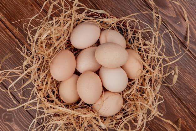 Vista superior de vários ovos de galinha no ninho em um fundo de madeira Foto gratuita