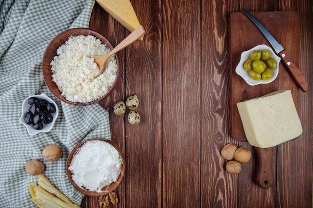 Vista superior de vários queijos e requeijão em uma tigela com nozes, ovos de codorna e azeitonas em conserva na tábua de madeira com uma faca na mesa rústica Foto gratuita