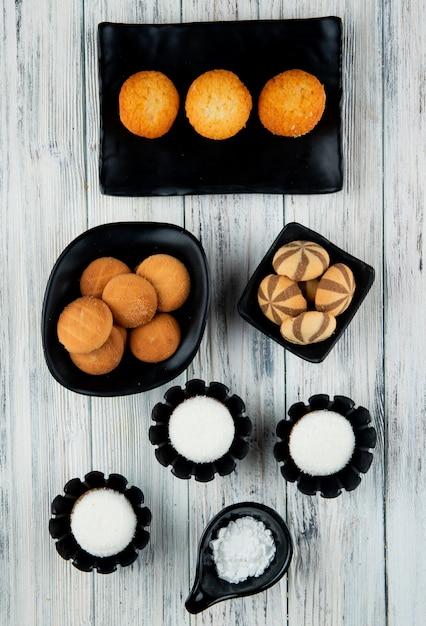 Vista superior de vários tipos de biscoitos doces e muffins em bandejas pretas sobre fundo de madeira Foto gratuita