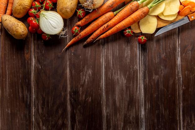 Vista superior de vegetais com cenouras e espaço para texto Foto gratuita