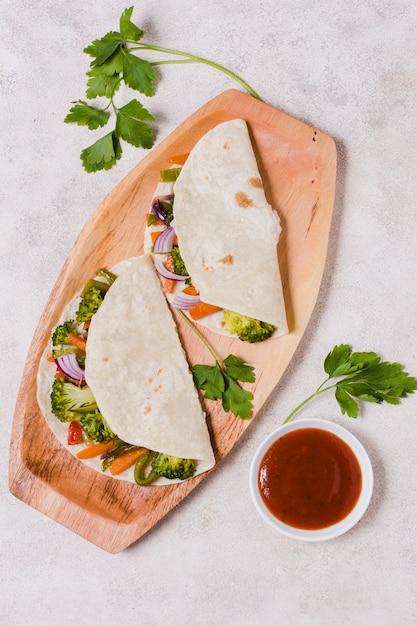 Vista superior de vegetais orgânicos envolto em pão árabe com molho Foto gratuita