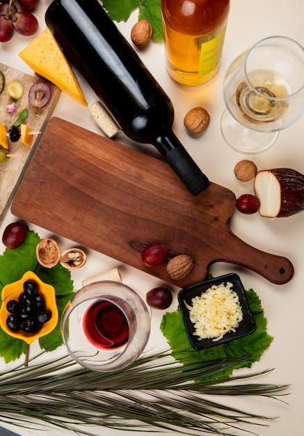 Vista superior de vinho tinto e vinho branco com placa de corte de noz de azeitona queijo parmesão ralado na mesa branca decorada com folhas Foto gratuita