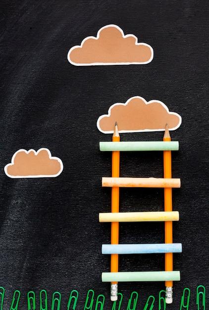 Vista superior de volta à escada da escola com lápis e nuvens Foto gratuita