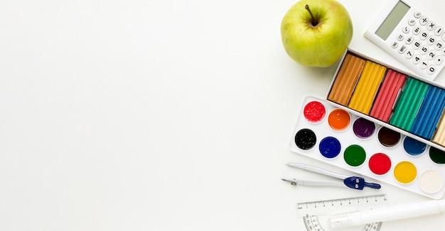 Vista superior de volta ao essencial da escola com aquarela e maçã Foto gratuita