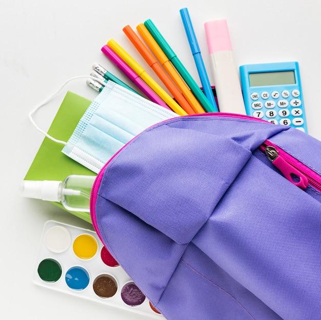 Vista superior de volta ao essencial da escola com mochila e calculadora Foto gratuita