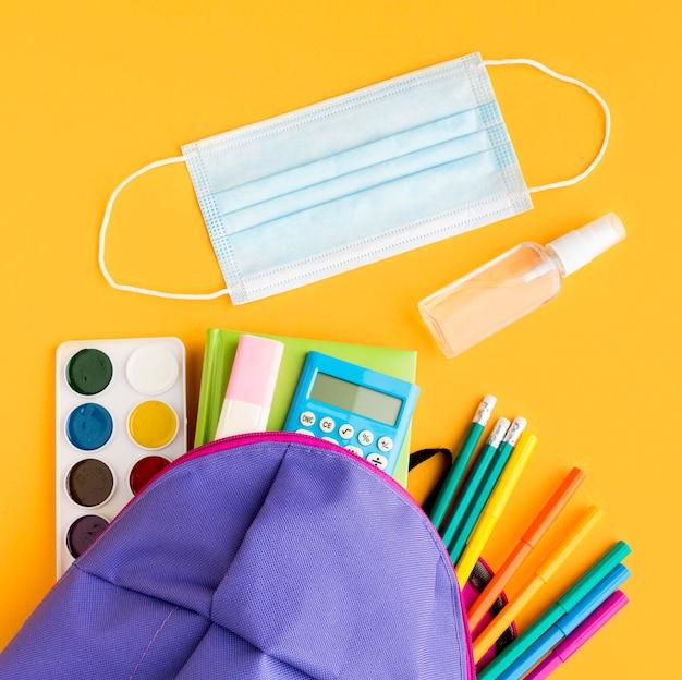 Vista superior de volta ao essencial da escola com mochila e máscara médica Foto Premium
