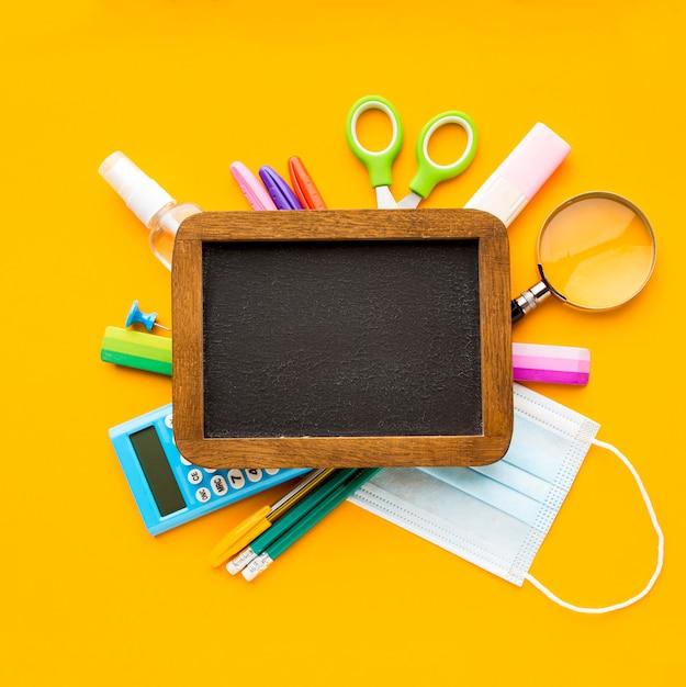 Vista superior de volta ao essencial da escola com quadro-negro e lápis Foto gratuita