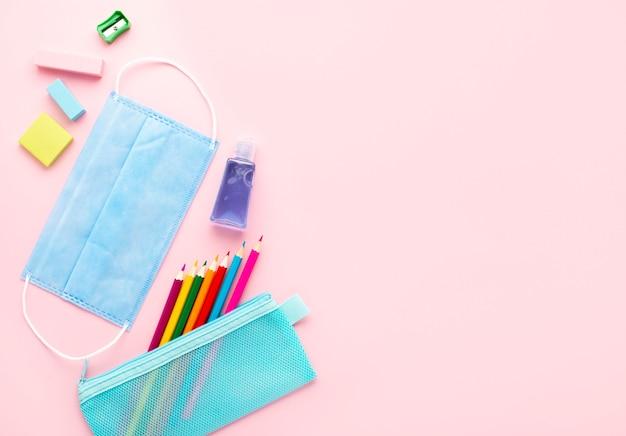 Vista superior de volta aos artigos de papelaria da escola com máscara médica e lápis coloridos Foto gratuita