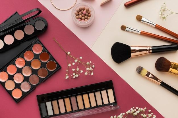 Vista superior decoração com produtos de beleza e fundo rosa Foto gratuita
