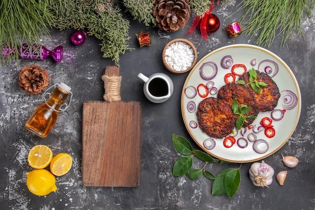 Vista superior deliciosas costeletas com anéis de cebola no fundo cinza prato de carne da foto Foto gratuita