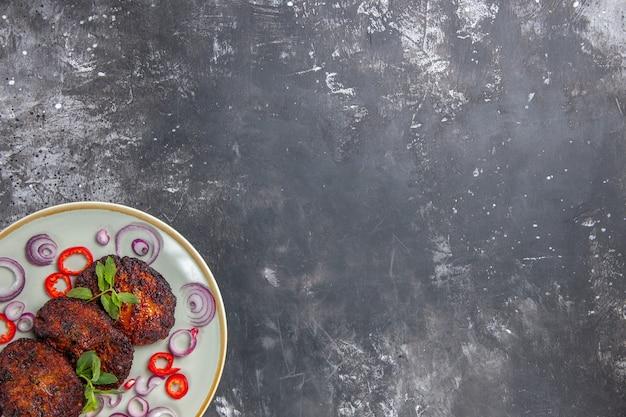 Vista superior deliciosas costeletas de carne com rodelas de cebola Foto gratuita