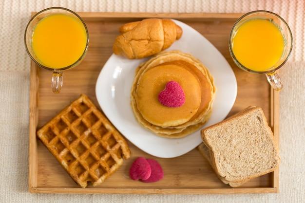 Vista superior delicioso café da manhã na cama Foto gratuita