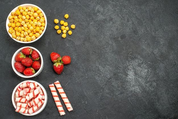 Vista superior deliciosos morangos com doces em um fundo preto com espaço livre Foto gratuita