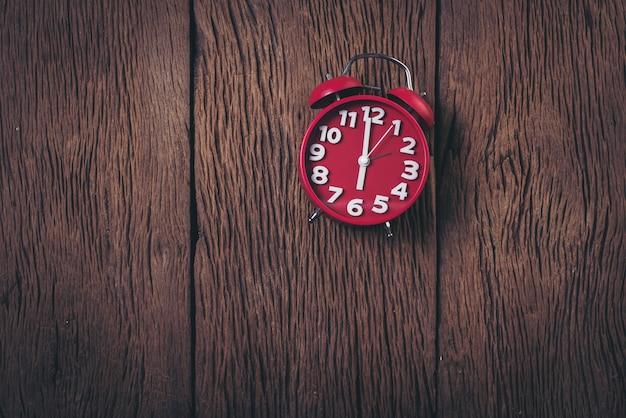 Vista superior despertador vermelho no fundo de madeira Foto gratuita