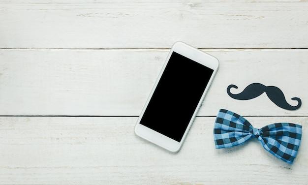 Vista superior dia do pai feliz. telefone móvel em fundo de madeira rústico. o pai de homen é bigode e gravata de ouro vintage. Foto gratuita
