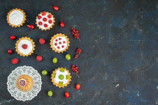 Vista superior distante bolinhos deliciosos com creme e frutas frescas na mesa de frutas escura Foto gratuita
