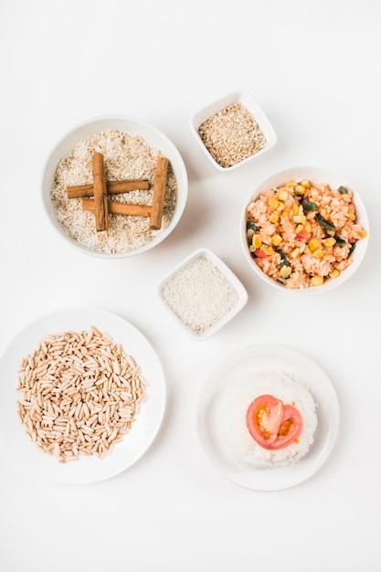 Vista superior do arroz tufado; arroz frito chinês e arroz cru com paus de canela Foto gratuita